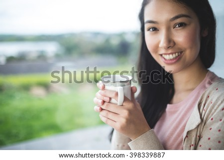 Portrait of happy woman near window with cup of coffee