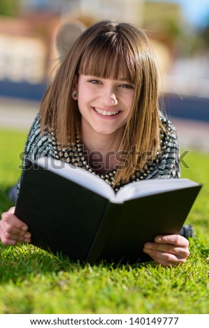 Portrait Of Happy Woman Reading Book In Park, Outdoors