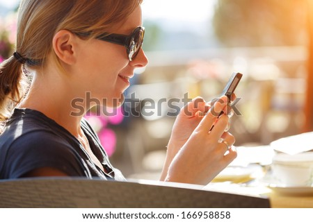 Portrait of happy woman reading off touch phone in cafe outdoors. - stock photo