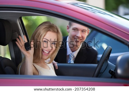 Portrait of happy woman showing key in car with salesman in background - stock photo