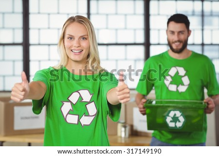 Portrait of happy woman showing thumbs up with colleague in background - stock photo
