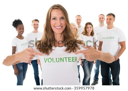 Portrait of happy woman showing volunteer text on tshirt with friends standing over white background