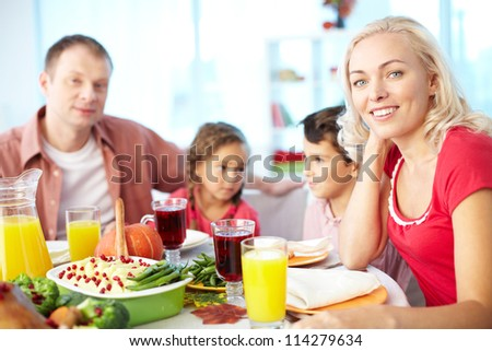 Portrait of happy woman sitting at festive table and looking at camera with her family on background - stock photo