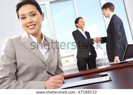 Portrait of happy woman sitting at workplace on background of business people?s handshake - stock photo