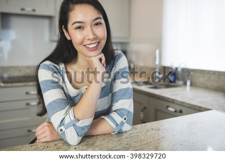 Portrait of happy woman sitting in kitchen with hand on chin