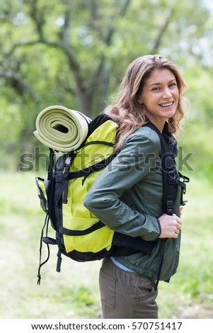 Portrait of happy woman standing with backpack in forest