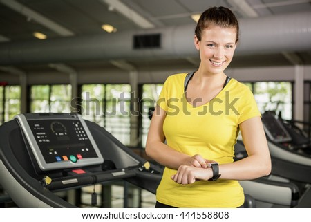 Portrait of happy woman using smart watch on treadmill at gym - stock photo