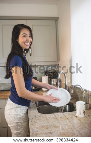 Portrait of happy woman washing up in the kitchen at home - stock photo