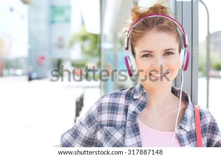 Portrait of happy woman wearing headphones while waiting at bus stop - stock photo