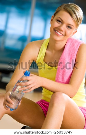 Portrait of happy woman wearing yellow tanktop looking at camera with smile in gym - stock photo