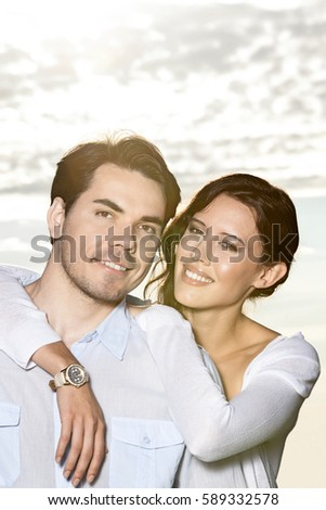 Portrait of happy woman with arm around man at beach