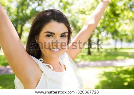 Portrait of happy woman with arms raised standing in park - stock photo
