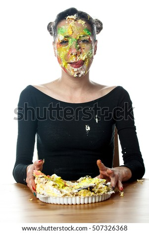 Portrait of happy woman with cake on her face