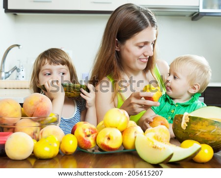 Portrait of happy woman with children  eating fruits at home
