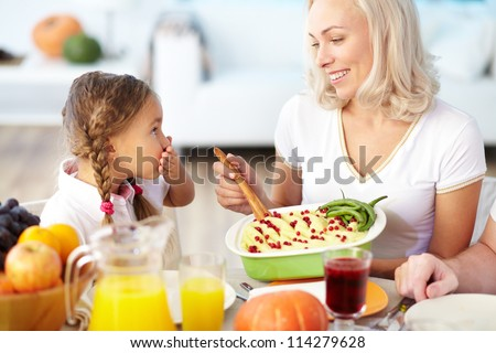 Portrait of happy woman with mashed potatoes and her daughter sitting at festive table