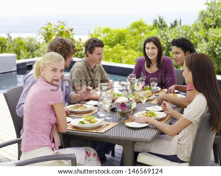 Portrait of happy woman with multiethnic friends enjoying meal at patio - stock photo