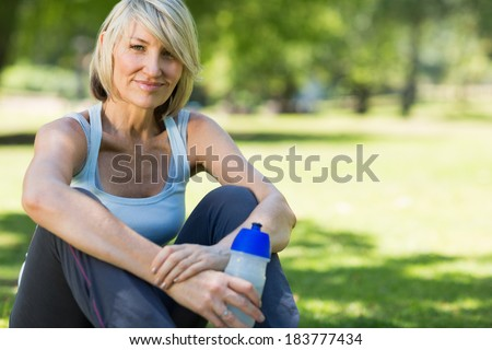 Portrait of happy woman with water bottle sitting in the park - stock photo