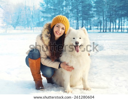 Portrait of happy woman with white Samoyed dog outdoors on the snow in winter day - stock photo