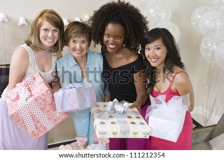 Portrait of happy women holding gifts at  party - stock photo