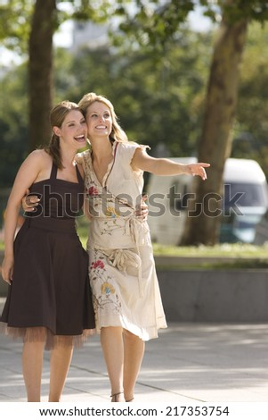 Portrait of happy women outdoors and woman pointing - stock photo