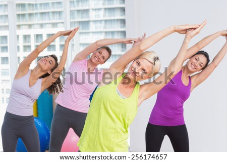 Portrait of happy women practicing stretching exercise at fitness studio