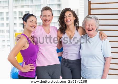 Portrait of happy women standing arms around in gym