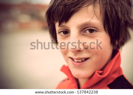 Portrait of happy 11 year old boy looking at camera with selective focus. Cross procesing effects. - stock photo