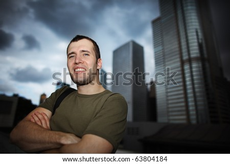 Portrait of happy young adult man over modern city background. Closeup, shallow DOF. - stock photo