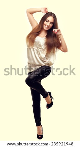Portrait of happy young adult woman dancing with her hands behind head. - stock photo