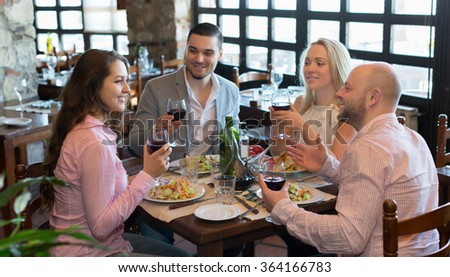 Portrait of happy young adults having dinner in restaurant. Focus on brunette girl