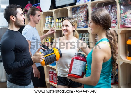 Portrait of happy young adults with sport nutrition products in shop