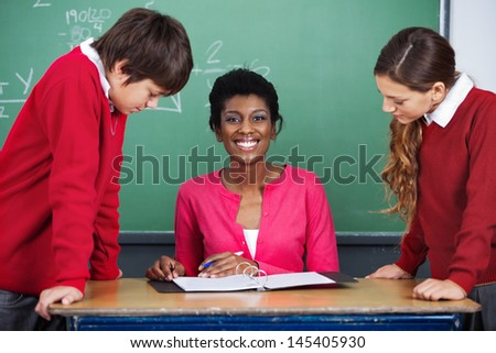 Portrait of happy young African American female teacher sitting at desk with students in classroom
