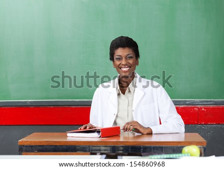 Portrait of happy young African American female teacher sitting with binder at desk in classroom - stock photo