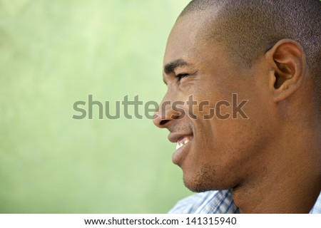 Portrait of happy young african american man looking away and smiling. Head and shoulders, copy space - stock photo