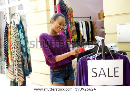 Portrait of happy young african american woman shopping for clothes at store - stock photo