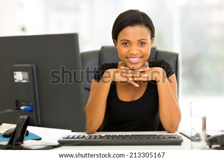 portrait of happy young african business woman sitting in office
