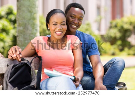 portrait of happy young african college couple outdoors - stock photo