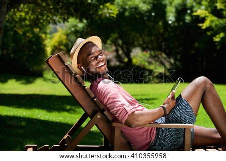 Portrait of happy young african man relaxing on chair outdoors with a digital tablet on a summer day - stock photo