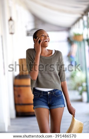 Portrait of happy young african woman walking and talking on mobile phone - stock photo
