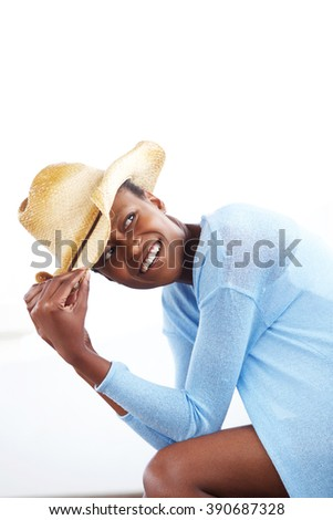 Portrait of happy young african woman wearing a cowboy hat and looking away - stock photo