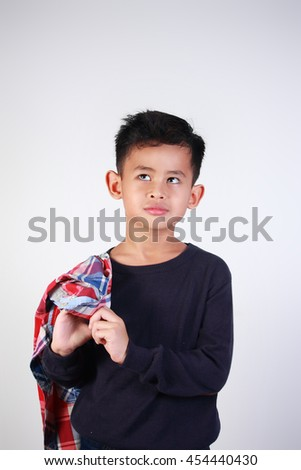 Portrait of happy young Asian boy looking up and dreaming while holding jacket on his shoulder - stock photo