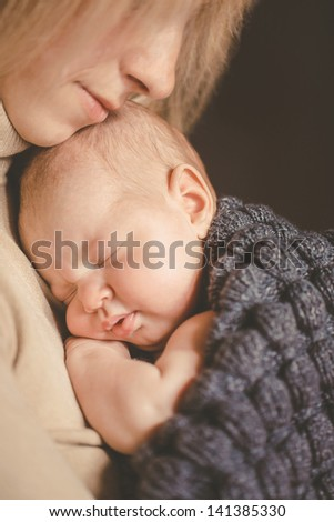 Portrait of happy young attractive mother lying with her baby on the bed at home - stock photo