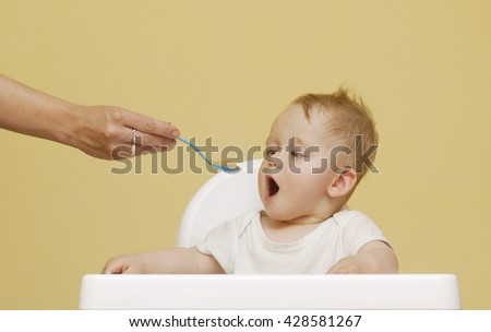 Portrait Of Happy Young Baby Boy In High Chair. The baby boy eating with spoon at home