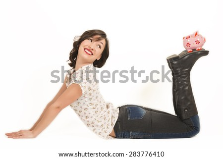 Portrait of happy young beautiful woman laying down holding pink piggy bank on her feet, studio shot on white background. Saving money concept - stock photo