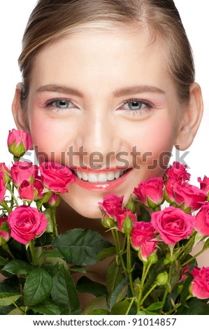 Portrait of happy young beautiful woman with pink roses and clear makeup