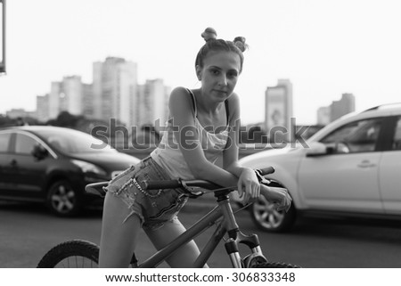 Portrait of happy young bicyclist reading book in city - stock photo