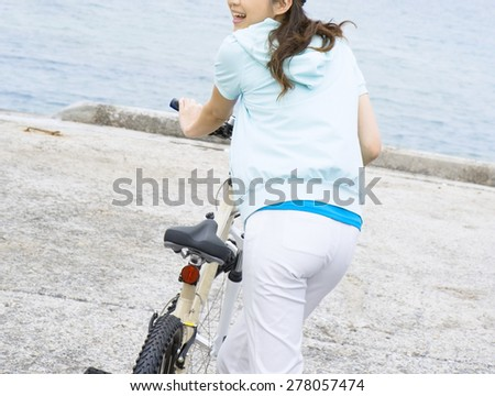 Portrait of happy young bicyclist riding - stock photo