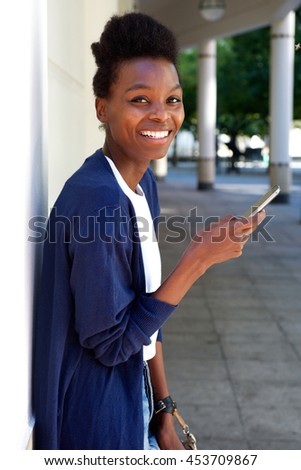 Portrait of happy young black woman standing outdoors with a mobile phone