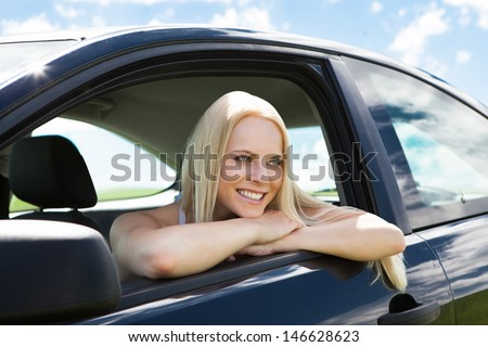 Portrait Of Happy Young Blonde Woman Leaning On Car Window