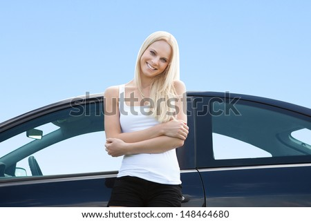 Portrait Of Happy Young Blonde Woman Standing Near Her Car - stock photo